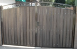 Decorative RV gate with dark brown frame and rustic cedar composite privacy slats