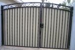 Arched decorative RV gate with hand-hammered Italian scrolls and plate steel for privacy
