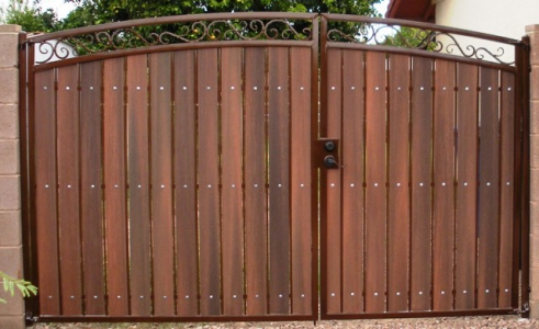 Arched, decorative, secure and useful RV gate.  The rust colored polyurethane paint and the redwood composite privacy slats comb