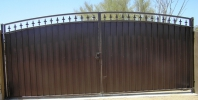 Decorative arched RV gate with plate steel privacy and fleur de lis spears