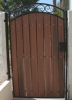 arched pedestrian gate showing redwood composite and black steel